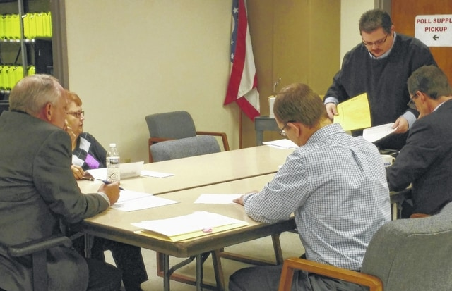 Outgoing Allen County Board of Elections director Ken Terry, right, goes over provisional ballots from the March 15 primary during the board of elections meeting Tuesday. Terry is being succeeded as director by former Champaign County elections Director Kathy Meyer.