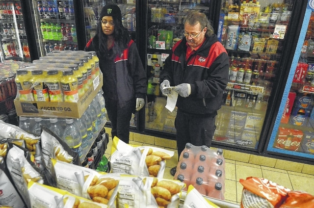 Coca-Cola employees Shanye Horne, left, and Calvin Chambers check a delivery to Star Gas Station on North Street in Lima at 5:30 a.m.