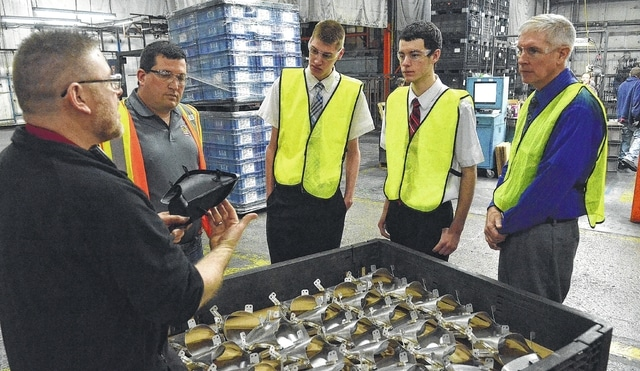 Brian Reynolds, far left, of Metokote Corp. in Lima explains the advance applications of coating to automobile parts to Kyle Lisk, 18, and Brandon Slate, 18, seniors at Delphos St. John's High School on Friday. Several students from Delphos St. John's got an opportunity to see the world's leader in advanced coating applications, operating more than 70 coating systems for more than 800 customers in 29 facilities worldwide. Students were able to observe the technologies in use and learn about careers available in MetoKote's high-tech custom coating technologies, as well as their additional services to manufacturing, such as aftermarket sheet metal labeling, masking development and utilization. MetoKote serves the automotive, agricultural and construction equipment, and truck and bus manufacturing, and other industries. The Link Lima Site Visit program was designed to provide high school students with an up-close, behind-the-scenes view of the world of steel fabrication and business. The goal is to allow students to observe the careers that are available to them with the right training after high school, and hopefully cultivate interest in those careers. Between Lisk and Slate are Eric Kerner of Metokote and Alan Unterbrink, a guidance counselor at St. John's.