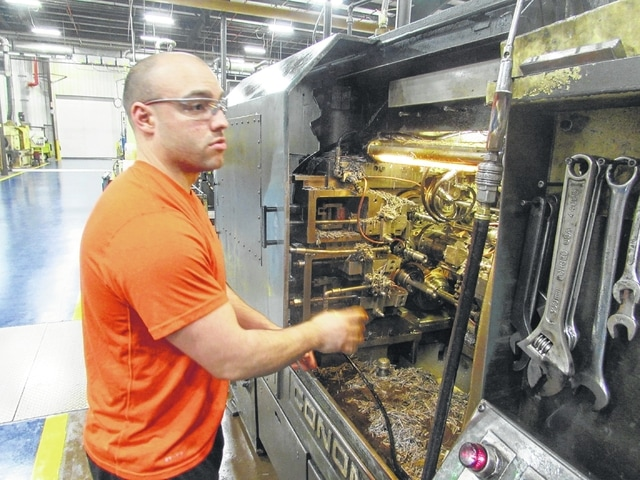Vanamatic employee Blake Williams, 24, cleans metal filings from an automatic screw machine during the second shift at Vanamatic in Delphos.