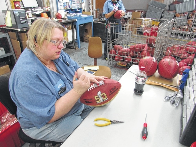Anita Clemons, 50, straightens a loose lace on a Super Bowl 50 championship football at the Wilson Sporting Goods football factory in Ada.