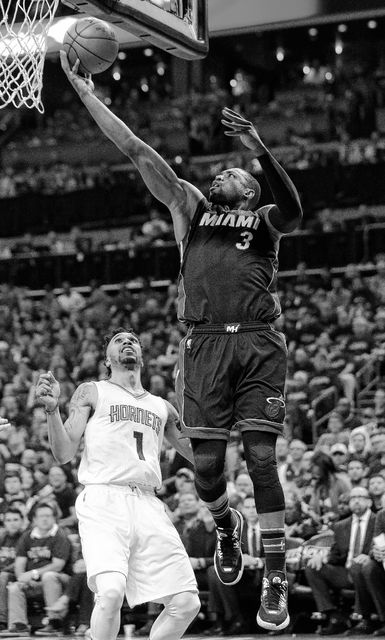 Miami's Dwyane Wade shoots over the Hornets' Courtney Lee during Friday night's playoff game in Charlotte, N.C.