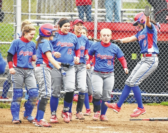 Crestview players wait for Averey McCoy to jump on home plate after she hit a solo home run during Thursday's game in Bluffton.