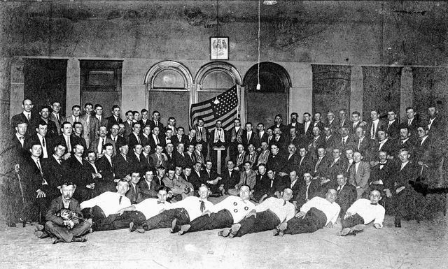 This undated photo shows the Lima group of the Order of Owls. The man sitting cross-legged on the floor on the left is holding an owl with his gloved hands.
