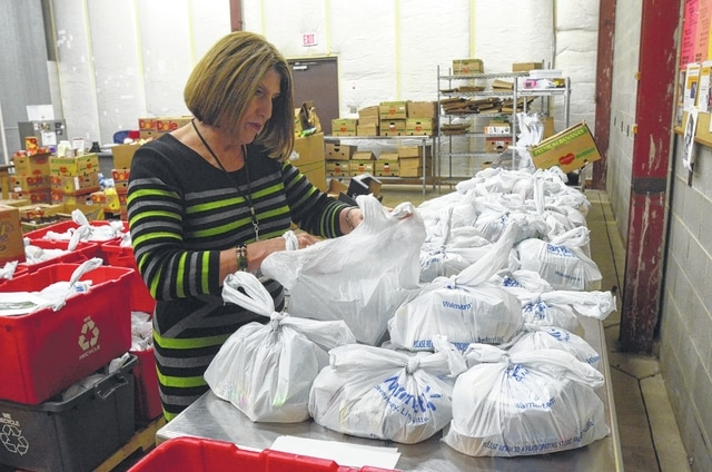 Linda Hamilton, CEO of the West Ohio Food Bank, looks through plastic bags of food and drinks that will be sent to needy children as part of a partnership with Allen County schools.