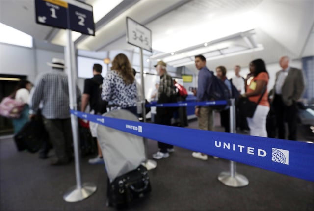Groups of passengers wait at a United Airlines gate to board a flight at O'Hare International Airport in Chicago. (AP Photo)