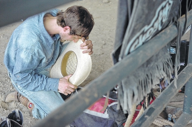 "Adam Miller, a bull rider from Dundee, Ohio, takes a few moments to pray Friday before the PBR Lima Invitational at the Allen County Fairgrounds in Lima. ""I couldn't do it without God's strength or help,"" Miller said."