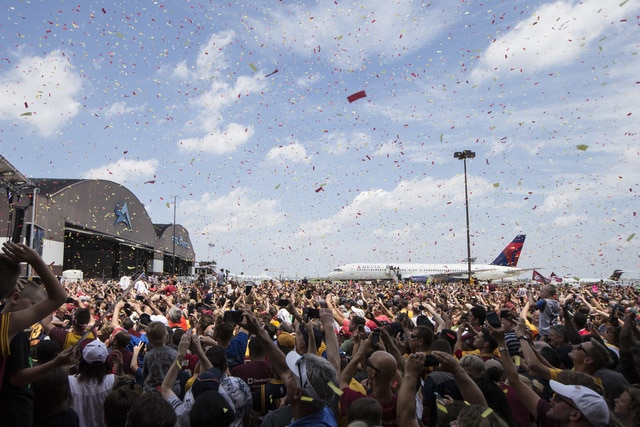 FILE - In this June 20, 2016, file photo, confetti is sprayed over the crowd as the Cleveland Cavaliers arrive at the airport after winning Game 7 of basketball's NBA Finals against the Golden State Warriors the previous night, in Cleveland. Since the moment superstar LeBron James and the Cavaliers clinched the NBA championship with an historic comeback to quench the city's 52-year professional title drought, Cleveland has been celebrating like never before. (AP Photo/John Minchillo, File)