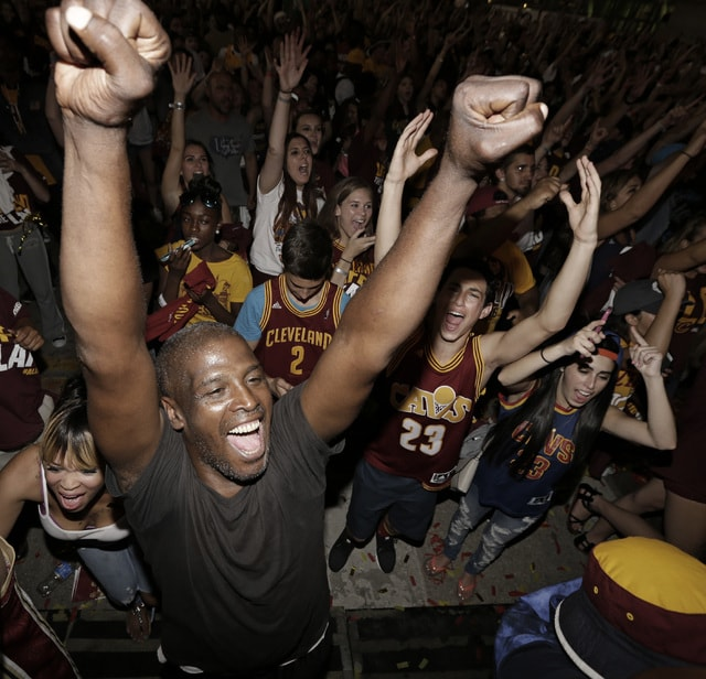 FILE - In this June 19, 2016, file photo, Cleveland Cavaliers fans celebrate after the Cavaliers defeated the Golden State Warriors 93-89 in Game 7 of the NBA basketball Finals in Cleveland. Since the moment superstar LeBron James and the Cavaliers clinched the NBA championship with an historic comeback to quench the city's 52-year professional title drought, Cleveland has been celebrating like never before. (AP Photo/Tony Dejak, File)