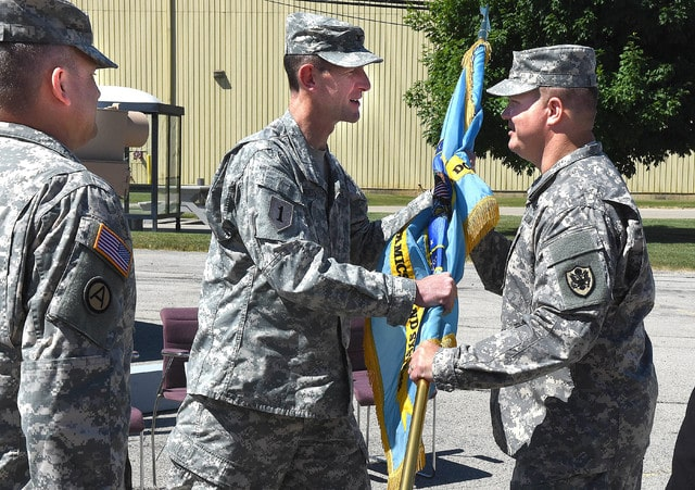 Col. Tommie Lucius, center, passes the colors to Lt. Col. Travis Adkins during the Change of Command Ceremony at General Dynamics Land Systems in Lima on Wednesday. To the left is departing Lt. Col. Matthew Hodge.