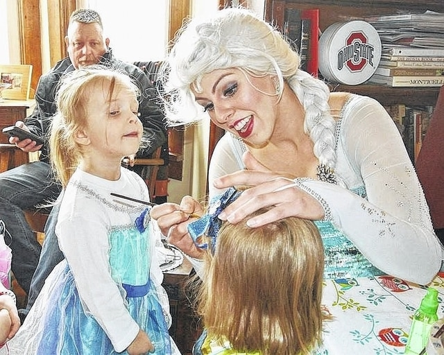 "Dressed as the ""Snow Queen"" fairy tale character, Art Me! owner Kirstene Adkins paints the face of a young girl at a recent birthday party in Columbus Grove."