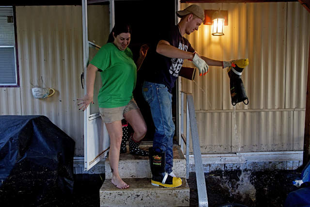 Shelley DeCarlo, 40, left, and Daniel Stover, 17, empty their boots of water as they enter the home of Laura Albritton to help her save some personal belongings from flood water in Sorrento, La., Saturday, Aug. 20, 2016.  Louisiana continues to dig itself out from devastating floods, with search parties going door to door looking for survivors or bodies trapped by flooding. (AP Photo/Max Becherer)