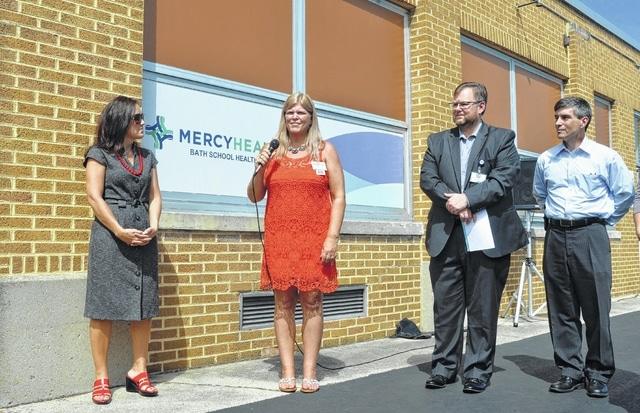 Mindy Wise, director of occupational health at St. Rita's Medical Center, speaks about the Mercy Health-Bath Local School Health Center during a ribbon-cutting ceremony Thursday. She is flanked by St. Rita's Chief Operating Officer Ronda Lehman, left, St. Rita's Health Partners President Dale Gisi, second from right, and Bath Superintendent Dale Lewellen.