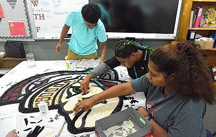 Lima Senior Alternative Program students Kayonna Stiggers, 17, left, works with Precious Green, 18, and Alina Williamson, 16, to glue pieces of small-cut glass, mirror and beads on a large mosaic Spartan head on Tuesday. Once the project is complete it will be hung in the hallway to help build Spartan pride.