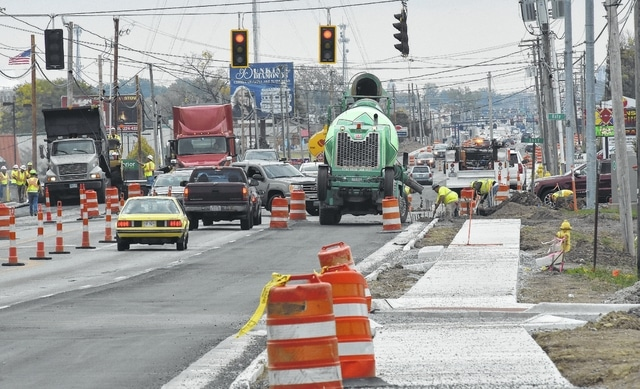 Local traffic weaves around barriers and construction workers at the Baty Road intersection of Elida Road.
