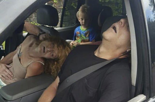 FILE - In this Sept. 7, 2016, file photo, released by the East Liverpool Police Department, a young child sits in a vehicle behind his grandmother, Rhonda Pasek and her boyfriend, James Acord, both of whom are unconscious from a drug overdose, in East Liverpool, Ohio. A judge has given relatives custody of the boy. The East Liverpool Review reports no one contested the granting of custody to the boy's great aunt and uncle during a hearing Monday, Dec. 19 in Columbiana County. (East Liverpool Police Department via AP, File)