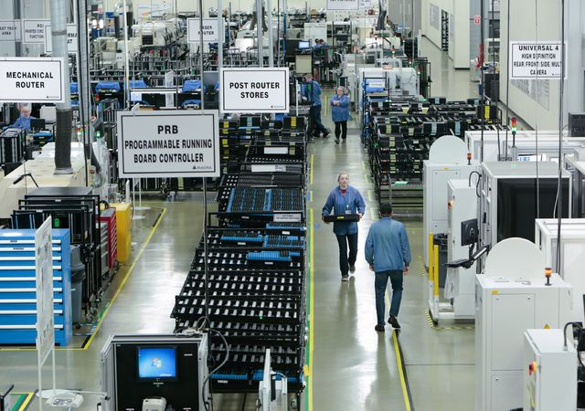 Workers assemble and test various camera systems made for automobiles at Magna Electronics in Holly, Mich. (Ryan Garza/Detroit Free Press/TNS)