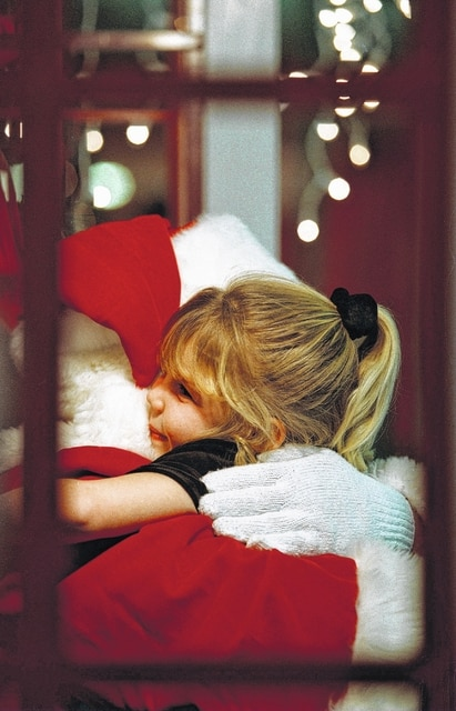 Kayli Lamb gives Santa a hug to conclude her visit at the Lima Mall in 1998. Lamb was 4 years old at the time.