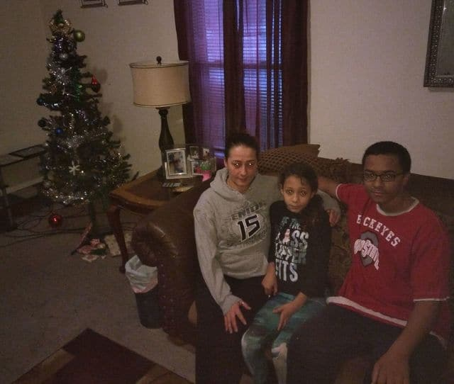 From left, Christy Colley, her daughter, Breonni Ellis, and son, JVeahn Ellis, sit in their living room Wednesday where three burglars broke into the home and stole the family's presents from under the Christmas tree.