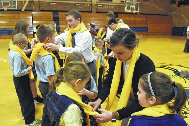 Delphos St. John's seniors, Derek Klausing, 18, and Madilynn Schulte, 18, help elementary school students with yellow National School Choice Week scarfs for a school photo on Wednesday in the gymnasium.