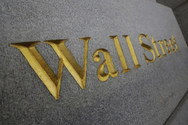FILE - In this Oct. 2, 2014, file photo, Wall Street is etched in the facade of a building in New York's Financial District.  Stocks are opening higher on Wall Street, Tuesday, Feb. 21, 2017,  as investors return from the holiday weekend in a buying mood. (AP Photo/Richard Drew, File)