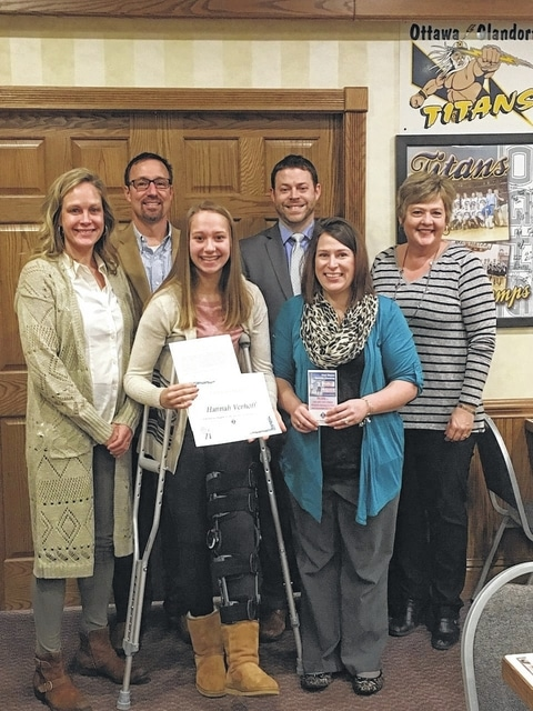 Hannah Verhoff, on crutches, center, receives a Character Award from the Putnam County Optimists. Ottawa-Glandorf High School principal Jayson Selgo, in jacket and tie, right, nominated Verhoff for the award.
