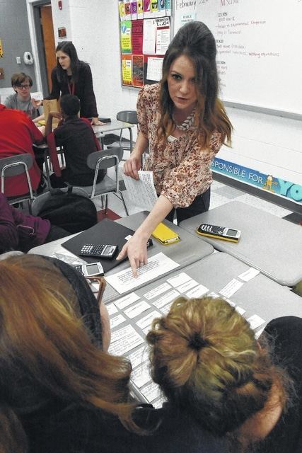 Theresa Guay, center, and Kristin Rhodes, left, works with students during a technology class at Lima Senior High School recently.