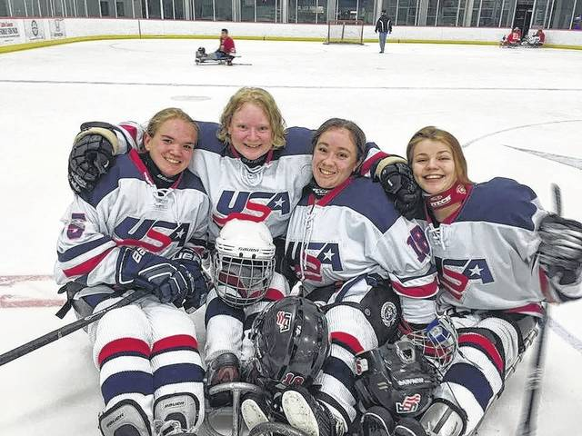 Kelli Anne Stallkamp, second from the left, poses with other USA National Sled Hockey team members after a recent match.