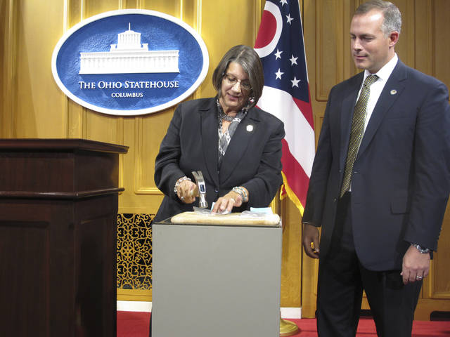 In this Sept. 17, 2015, file photo, state Rep. Nickie Antonio, left, D-Lakewood, demonstrates tamper resistant pain pills by unsuccessfully trying to pulverize them with a hammer, as state Rep. Robert Sprague, R-Findlay, awaits his turn during a news conference at the Statehouse in Columbus. Pharmaceutical lobbyists pressed to drive down cost estimates on an Ohio proposal requiring Medicaid and other insurers to cover harder-to-manipulate forms of prescription painkillers known as abuse-deterrent opioids, according to emails obtained by The Associated Press through a public records request.