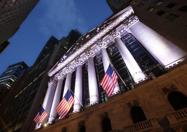 FILE - In this Oct. 8, 2014, file photo, American flags fly in front of the New York Stock Exchange. World stocks fell Tuesday, April 18, 2017, amid concerns about the security situation on the Korean Peninsula, France's upcoming presidential election, and Britain's surprise decision to hold a general election. (AP Photo/Mark Lennihan, File)