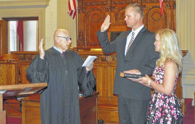 Retired Municipal Court Judge Michael O'Malley swears in Keith Schierloh as judge of Putnam County Common Pleas Court during a ceremony Saturday morning. Schierloh's wife, Traci, stands by his side.