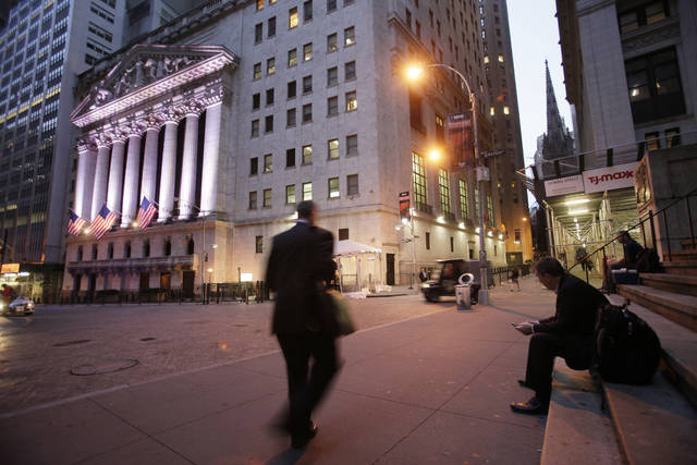 """FILE - In this Oct. 8, 2014, file photo, a man walks to work on Wall Street, near the New York Stock Exchange, in New York. Shares edged higher Monday, May 15, 2017, in Europe and Asia, despite worries of disruptions from the """"WannaCry"""" ransomware cyberattack over the weekend. (AP Photo/Mark Lennihan, File)"""