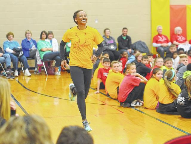 Diana Patton runs a lap around students as she reflects how her faith has pulled her through the challenges of life. She was the keynote speaker Friday as Positive Addictions Week concluded for Lima Catholic Schools. Richard Parrish | The Lima News