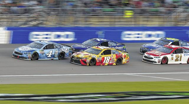 Kevin Harvick (4), Kyle Busch (18) and others are bunched up during a restart in the NASCAR Monster Cup auto race at Kansas Speedway in Kansas City, Kan., Saturday, May 13, 2017. (AP Photo/Orlin Wagner)