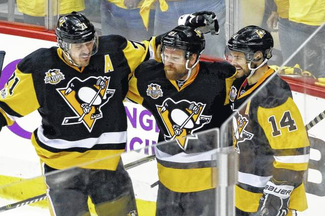 Pittsburgh Penguins' Phil Kessel, center, celebrates with teammates Evgeni Malkin (71) and Chris Kunitz (14) after scoring against the Ottawa Senators during the third period of Game 2 of the Eastern Conference final in the NHL hockey Stanley Cup playoffs, Monday in Pittsburgh.