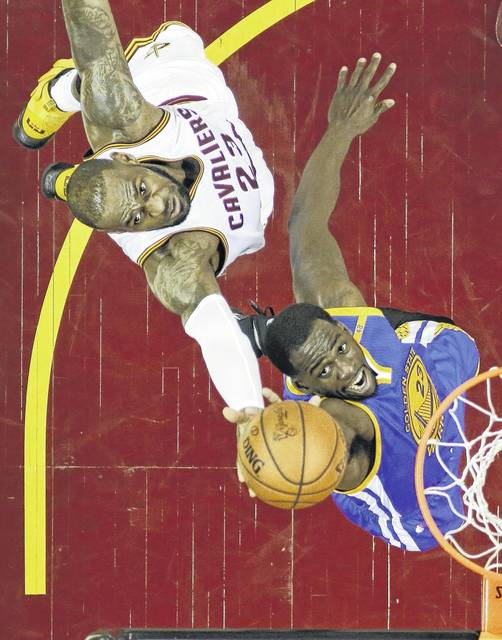 Golden State's Draymond Green, right, drives to the basket Friday night against the Cavaliers' LeBron James during Game 4 of the NBA Finals in Cleveland.
