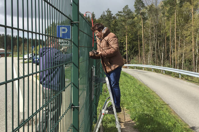 FILE - In this April 25, 2016 file photo Christina Wagner sells sausages through a fence next to the Autobahn near the town of Rodaborn. Authorities refused to give Wagner a permit to operate at the site, so she operates on an adjacent lot and passes sausages through the fence. German news agency dpa reported Thursday, June 15, 2017 that authorities are now threatening to issue Wagner with fines until she stops selling sausages at the site. (Andreas Hummel/dpa via AP, file)