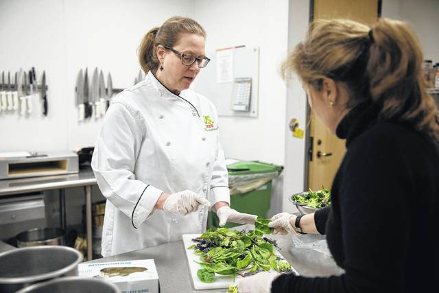 Chef Kathleen Hoffman, left, and product developer Ebru Basaydin look through mixed greens May 11 at US Foods in Rosemont, Ill. Companies such as US Foods use pop culture and health trends to help determine the next food fad.