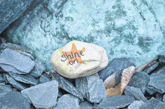 By Bryan Reynolds | The Lima News A painted stone is placed at the foot of the statue in Lengerich Garden on West Auglaize Street in Wapakoneta. West Auglaize Street and the Temple of Tolerance are two focal points for the stones right now, Lisa Schott, co-owner of Thrifty Treasures, said.