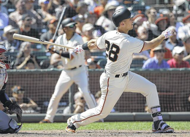 The Giants' Buster Posey hits a two-run double against Cleveland during the eighth inning of Wednesday's game in San Francisco.