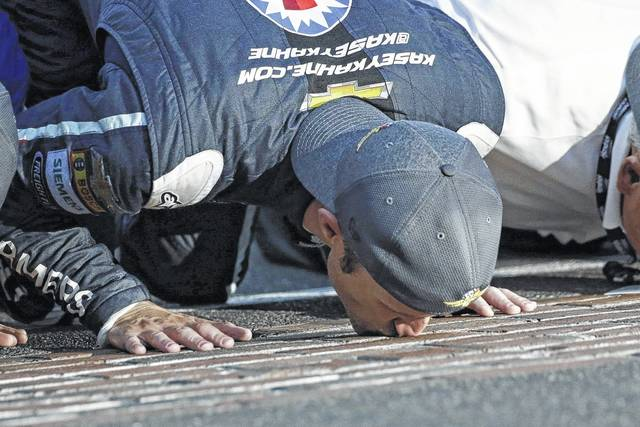 Kasey Kahne (5) kisses the yard of bricks on the start/finish line after winning Sunday's Brickyard 400 at Indianapolis Motor Speedway in Indianapolis.