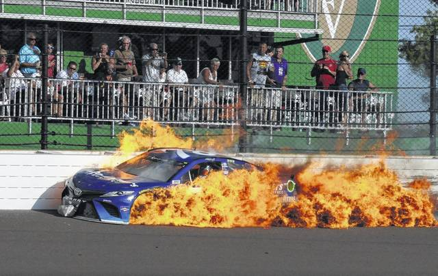 The car driven by Martin Truex Jr. burns after a crash with Kyle Busch during Sunday's Brickyard 400 at Indianapolis Motor Speedway in Indianapolis.