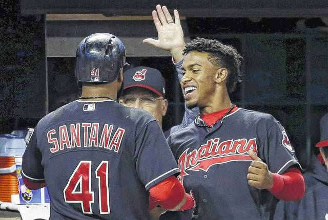 Francisco Lindor congratulates Indians teammate Carlos Santana after Santana hit a solo home run in the eighth inning of Monday night's game against Cincinnati in Cleveland.