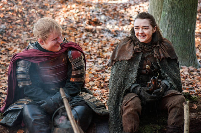 """This image released by HBO shows Ed Sheeran, left, and Maisie Williams in a scene from """"Game of Thrones."""" Sheeran appeared as a Lannister soldier leading a group in song in the season premiere of the hit HBO fantasy drama, which debuted on the premium cable channel Sunday night."""
