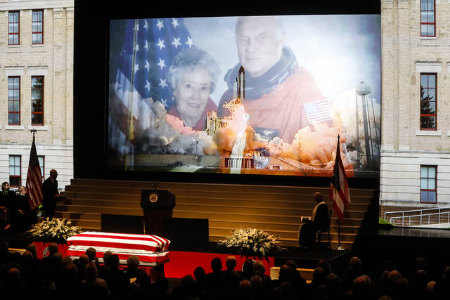 FILE – In this Dec. 17, 2016, file photo, the casket of U.S. Sen. John Glenn rests below an image of the astronaut and his wife, Annie, and the STS-95 space shuttle launch during his funeral ceremony at The Ohio State University in Columbus, Ohio. Glenn's devotees are pushing forward with ideas for memorials and honors as the anniversary of the astronaut's birth arrives Tuesday, July 18, 2017, for the first time since his death on Dec. 8, 2016, at age 95. (AP Photo/John Minchillo, File)