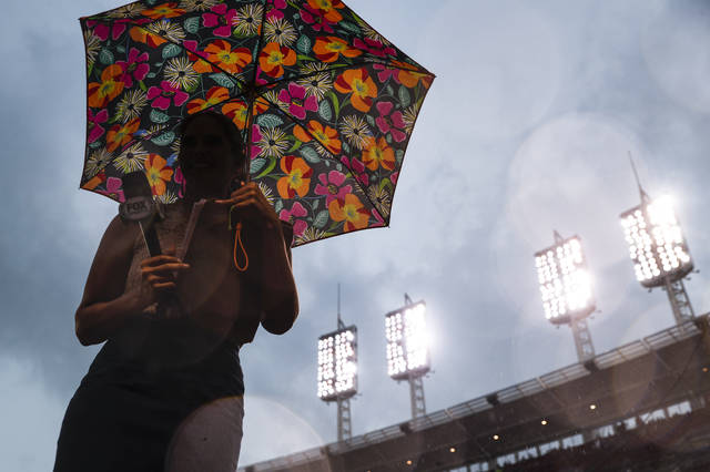 A reporter stands under her umbrella during a rain delay before a baseball game between the Cincinnati Reds and the Miami Marlins, Friday, July 21, 2017, in Cincinnati. (AP Photo/John Minchillo)
