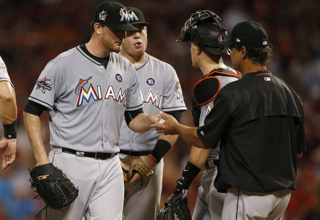 Miami Marlins starting pitcher Chris O'Grady, left, is pulled by manager Don Mattingly, right, during the fifth inning of a baseball game against the Cincinnati Reds on Saturday, July 22, 2017, in Cincinnati. (AP Photo/Gary Landers)