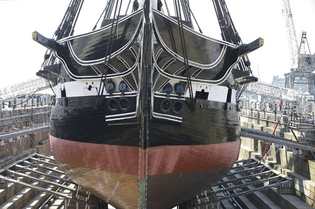 "ADDS THAT THIS IS THE OLDEST COMMISSIONED WARSHIP STILL AFLOAT - In this Monday, July 17, 2017 photo Bob Gerosa, the 74th Commander of USS Constitution, ""Old Ironsides,"" the world's oldest commissioned warship still afloat, stands beside the vessel while it sits in dry dock in Boston after a more then two year long restoration. The ship is scheduled to be refloated overnight Sunday July 23, 2017 and be docked back at its berth Monday morning. (AP Photo/Stephan Savoia)"