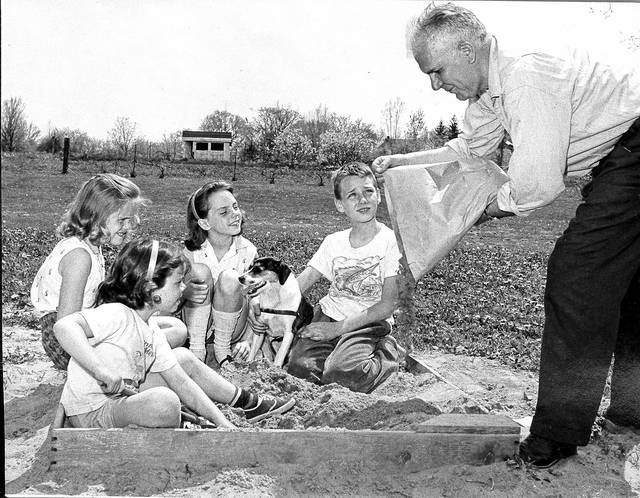 Claude Ebner helps fill a sandbox in 1962.