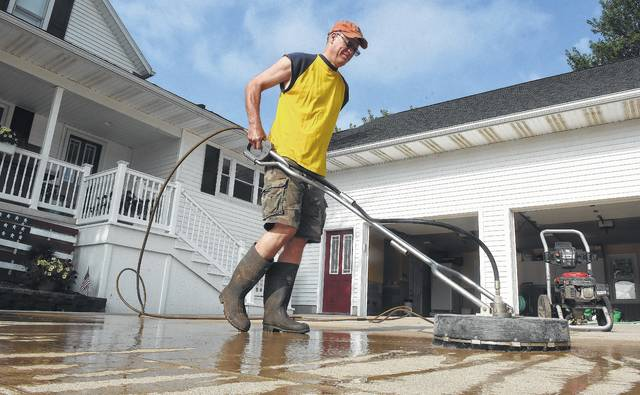 Dennis Maas, of Ottawa, uses a concrete power scrubber Monday to clean river mud from his driveway after the Blanchard River floodwater receded. Maas raised his house after the 2007 flood, which kept floodwater out of his home.